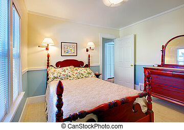 Beautiful romantic classic blue bedroom with red wood bed and dresser.