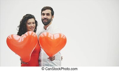 Beautiful romantic couple isolated on white background. An attractive young woman and beautiful hands raise balloons in the shape of the heart. Valentine's Day