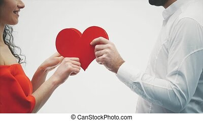 Beautiful romantic couple isolated on white background. An attractive young woman and handsome hand hold red hearts in their hands exchanged by them.