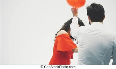 Beautiful romantic couple isolated on white background. An attractive young woman and handsome knock each other with balloons in the shape of the heart in their hands. Smiling. Happy Valentine