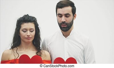 Beautiful romantic couple isolated on white background. An attractive young woman and handsome man hold red hearts in their hands. Valentine's Day