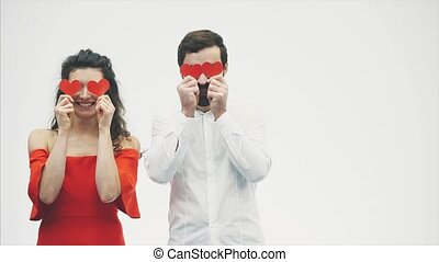 Beautiful romantic couple isolated on white background. An attractive young woman dressed in a red dress, a handsome man in a white shirt.