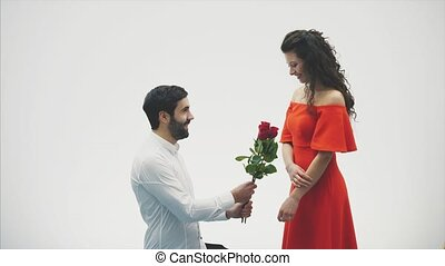 Beautiful romantic couple isolated on white background. An attractive young woman wearing red roses in a dress and a beautiful man in a white shirt gives the rose with love and tenderness. Valentine's Day