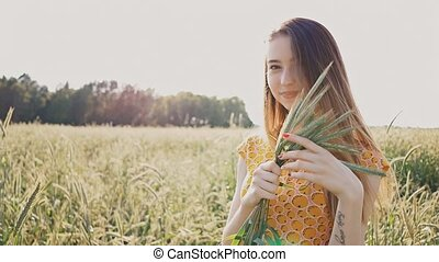 Beautiful romantic girl holding green wheat ears in her hand. A girl in a field in the rays of the summer sun. Pleasure. Nature.