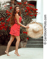 Beautiful Romantic girl with red lips wears dress enjoying life in blossom park. Attractive model jumping with straw summer hat.