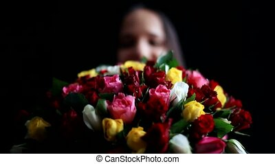 Beautiful romantic woman with a large bouquet of flowers in her arms smelling a fragrant colorful roses on black background.