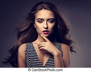 Beautiful romantic woman with bright makeup and wind long hair, pink lipstick posing in striped dress on grey background. Closeup portrait