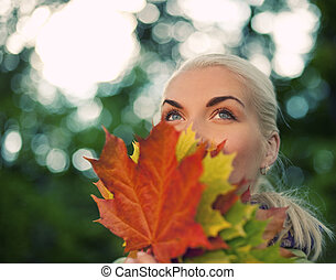 Beautiful romantic woman with golden autumn leaf close-up portrait