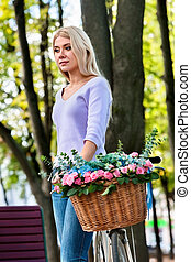 Beautiful romantic young woman on bike in park