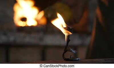 Beautiful rose is placed on a steel anvil covered with flame...
