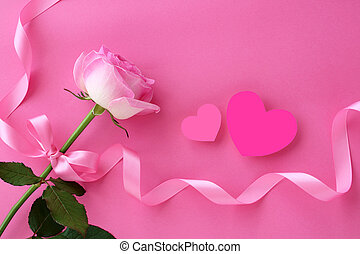 Beautiful rose with handmade heart and ribbon on pink background, top view