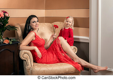 Beautiful royal woman in a luxurious dress with her daughter. In room.