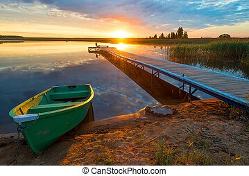 beautiful rural landscape - a wooden pier and a boat in the rays of the setting sun