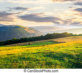 beautiful rural scenery in mountains at sunrise. haystack on...