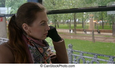 Beautiful sad girl looks through the window of a tram