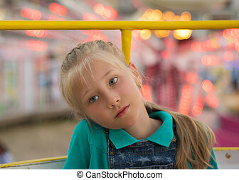 Beautiful sad girl on the background of amusement Park lights.