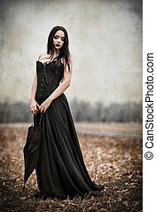 A beautiful sad goth girl holds black umbrella. Grunge texture effect
