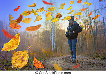 Beautiful sad lonely girl  walking away in autumn forest.