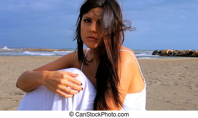 Beautiful sad woman on the beach
