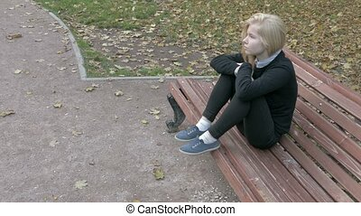 Beautiful sad woman sitting in city park