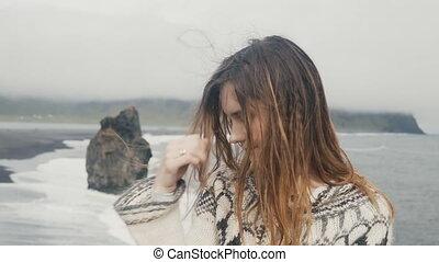 Beautiful sad woman thinking on the black beach in Iceland,...
