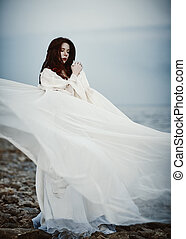 Beautiful sad young woman in white dress standing on sea beach