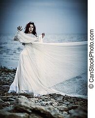 Beautiful sad young woman in white dress standing on sea coast