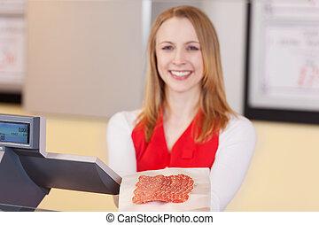 Beautiful saleswoman offering sliced salami