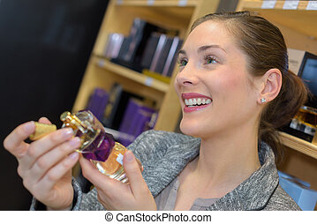 beautiful saleswoman showing beauty products to male customer