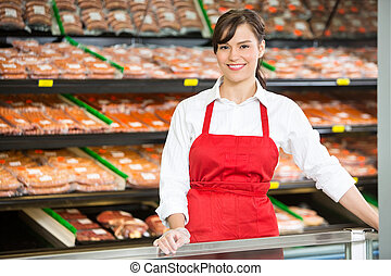 Beautiful Saleswoman Standing At Counter In Butcher's Shop -...