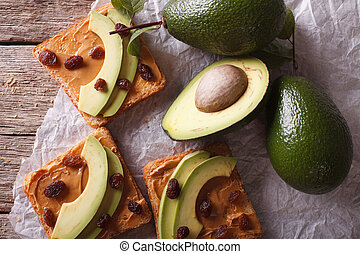 Beautiful sandwiches with avocado, peanut butter closeup. Horizontal top view