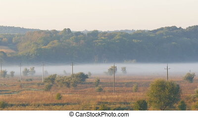 Beautiful scenic landscape of fog over the village plain. Power lines against the background of autumn fog