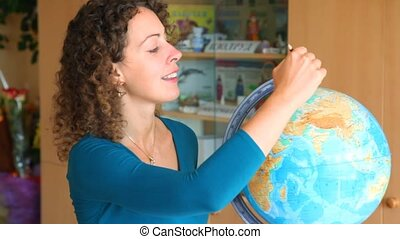 beautiful schoolteacher selecting continents and countries on globe