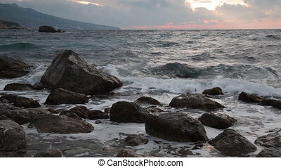 Beautiful sea landscape with waves and stones at sunrise
