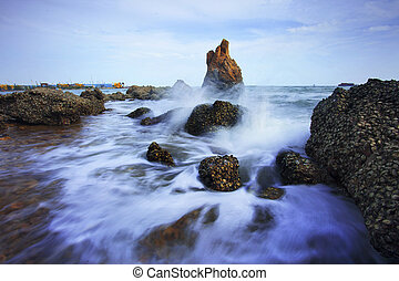 beautiful sea scape of waves splashing on rock use for multipur
