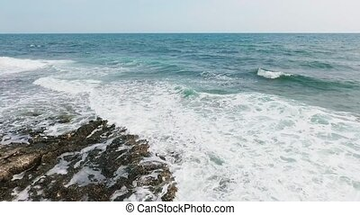 Beautiful sea waves. Aerial shot, flying over the rolling waves breaking on the rocks