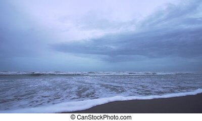 Beautiful sea waves in slow motion on the sand of the beach at blue sunset