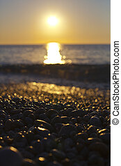 Beautiful seascape, amazing view of pebble coastline in mild sunset light.