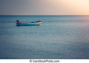 Beautiful seascape view of fishing boat floating on the sea with sunset light in the background. (Selective focus)