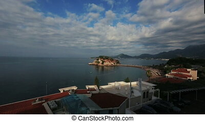 Beautiful seascape with cloudy sky and ancient town on background in Montenegro, Budva