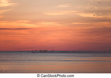 Beautiful seascape with people watching the sunset over the sea