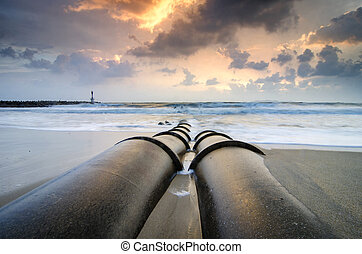 beautiful seascape with soft waves hitting concrete drainage pipe on the beach over sunrise background and dramatic dark clouds