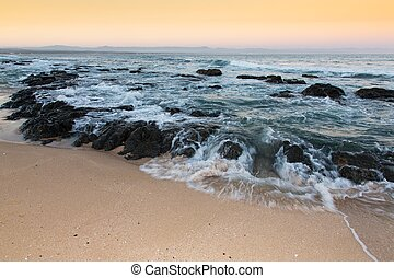 Rough sea and golden sand at the rugged coast in South Africa
