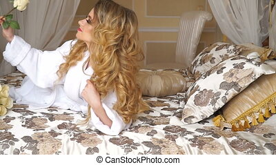 Beautiful seductive woman flirting with the camera lying on the bed with a big bouquet of white roses in White bathrobe looking up with a coquettish look