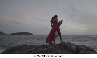 Beautiful seductive woman in red dress enjoying herself on rocks by the sea - video in slow motion