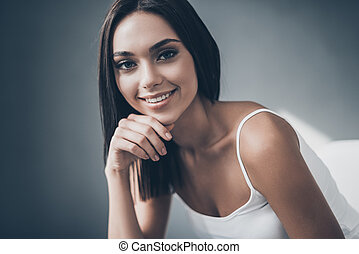 Beautiful seductress. Attractive young woman holding hand on chin and looking at camera with smile while sitting against grey wall