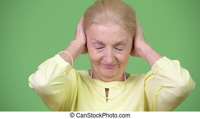 Beautiful senior businesswoman covering ears as three wise...