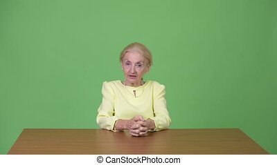 Beautiful senior businesswoman presenting something against wooden table