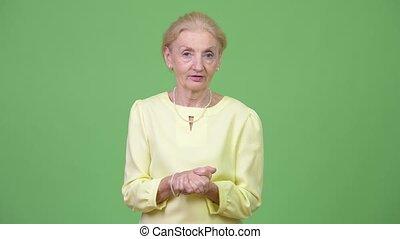 Beautiful senior businesswoman presenting something