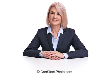 senior businesswoman sits at the desk